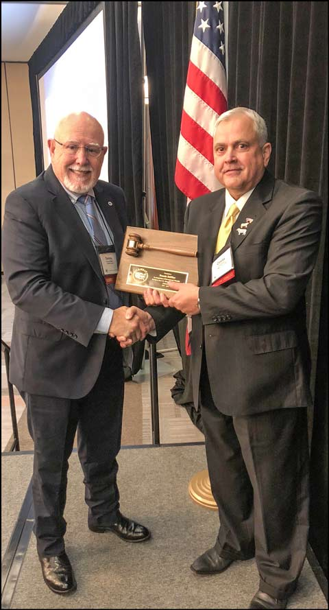 Newly elected US Meat Export Federation Chairman Conley Nelson (right) presents a ceremonial gavel to outgoing chair Dennis Stiffler.
