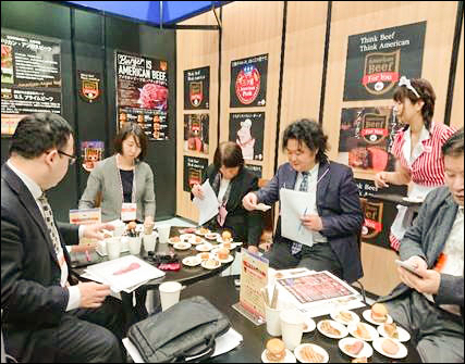 Representatives of supermarket chains and other retail outlets in Japan sample US pork and beef at USMEF's Supermarket Trade Show booth.